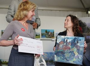 KJW02583b Artist Susan Isaac winning first prize in Oil Painting at Paint Out Norfolk, presented by judge Francesca Vanke